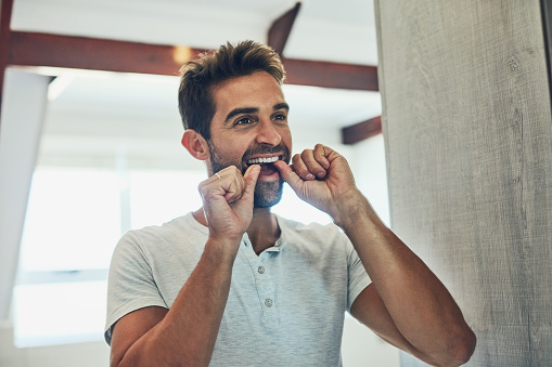 A man flossing his teeth and gums for better gum maintenance.